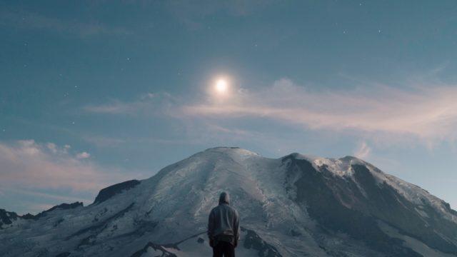 高い山と太陽を見つめる人物