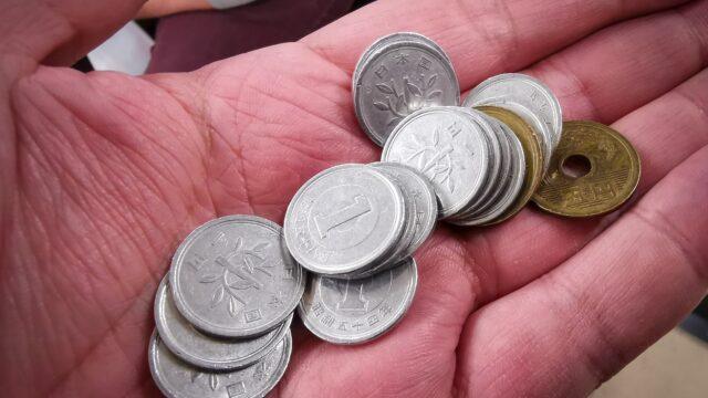 一円玉が10数枚と五円玉が手のひらに乗っている