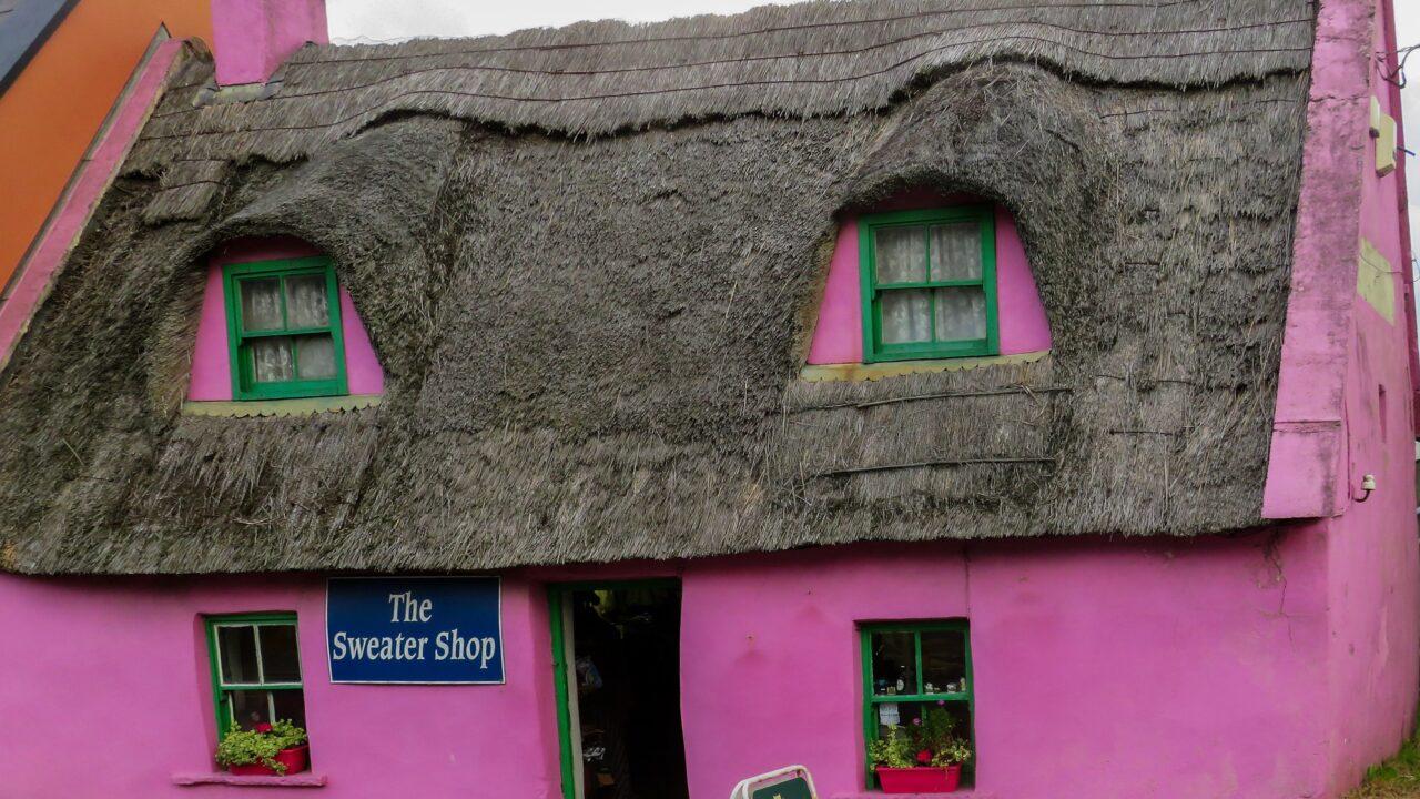 茅葺きのピンクの外壁の窓のあるショップ