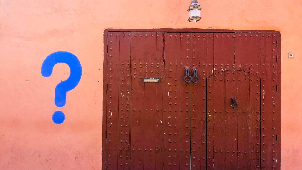 木のドアのオレンジの壁に青いクエスチョンマーク