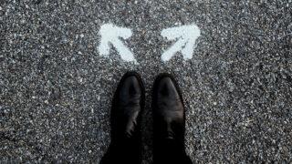 白い矢印サインが2つ黒い靴の前に書かれている