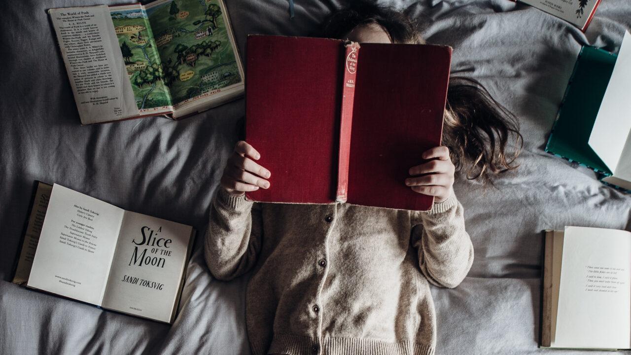 女の子が寝転んで読書している