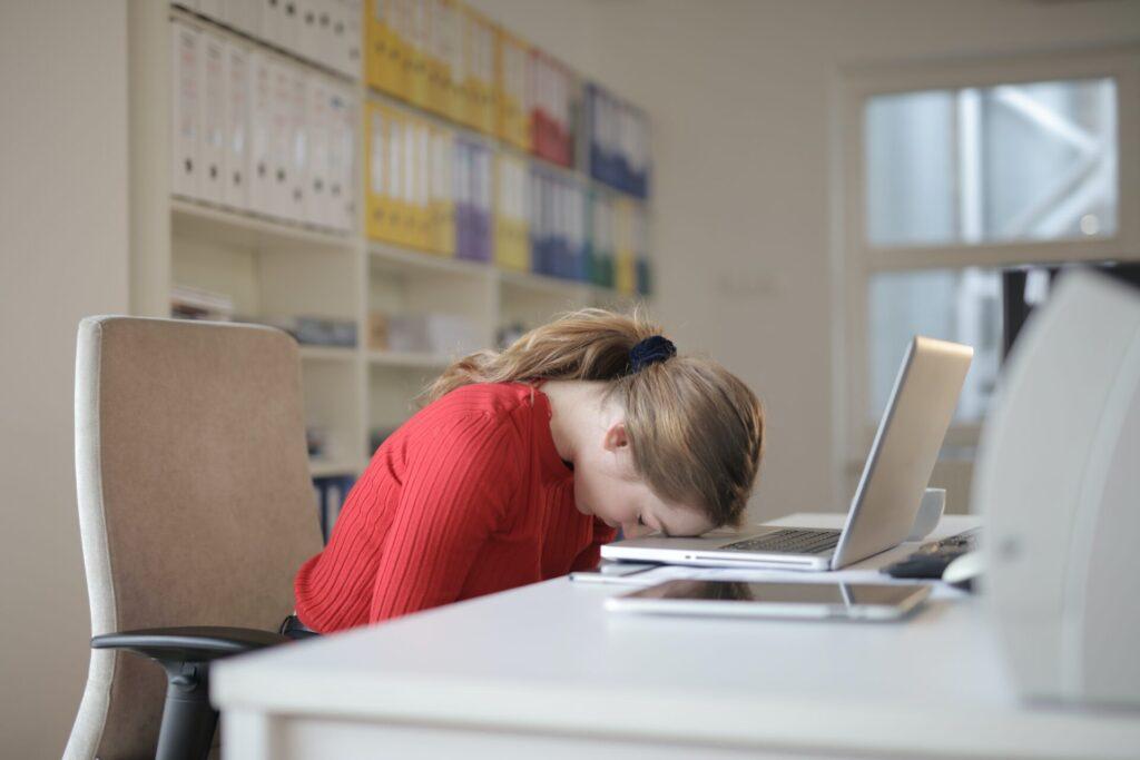 赤いトップを着た白身女性が疲れて顔をPCに突っ伏してる
