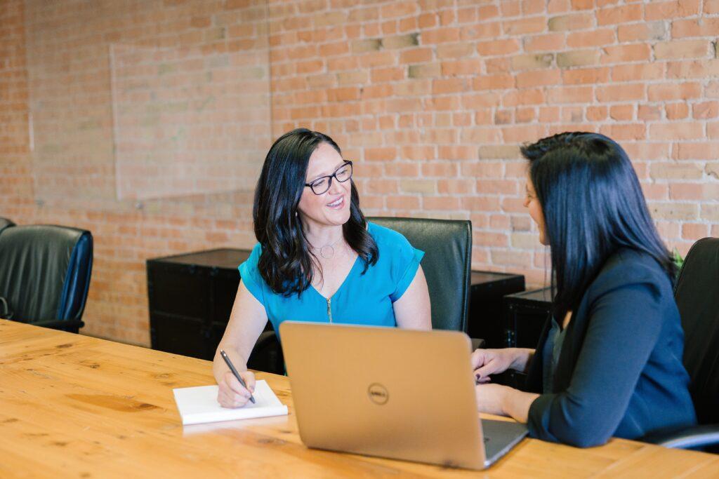 ブルーの半袖を着た黒髪の中年女性と黒髪の黒いジャケットを着た女性がテーブルを前にオフィスで話している