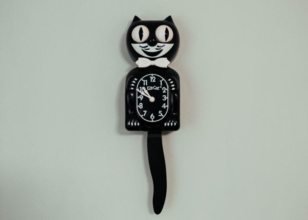 黒い猫の壁時計が白い壁にかかっている
