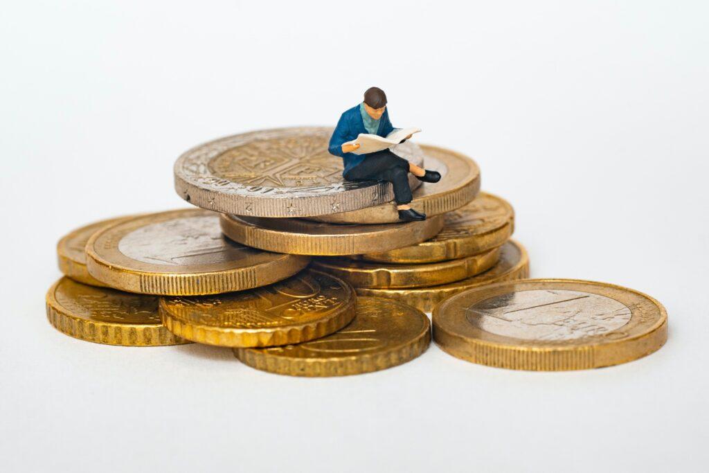 数枚の重なった金貨の上に本を読んでいる男性のフィギアが座っている