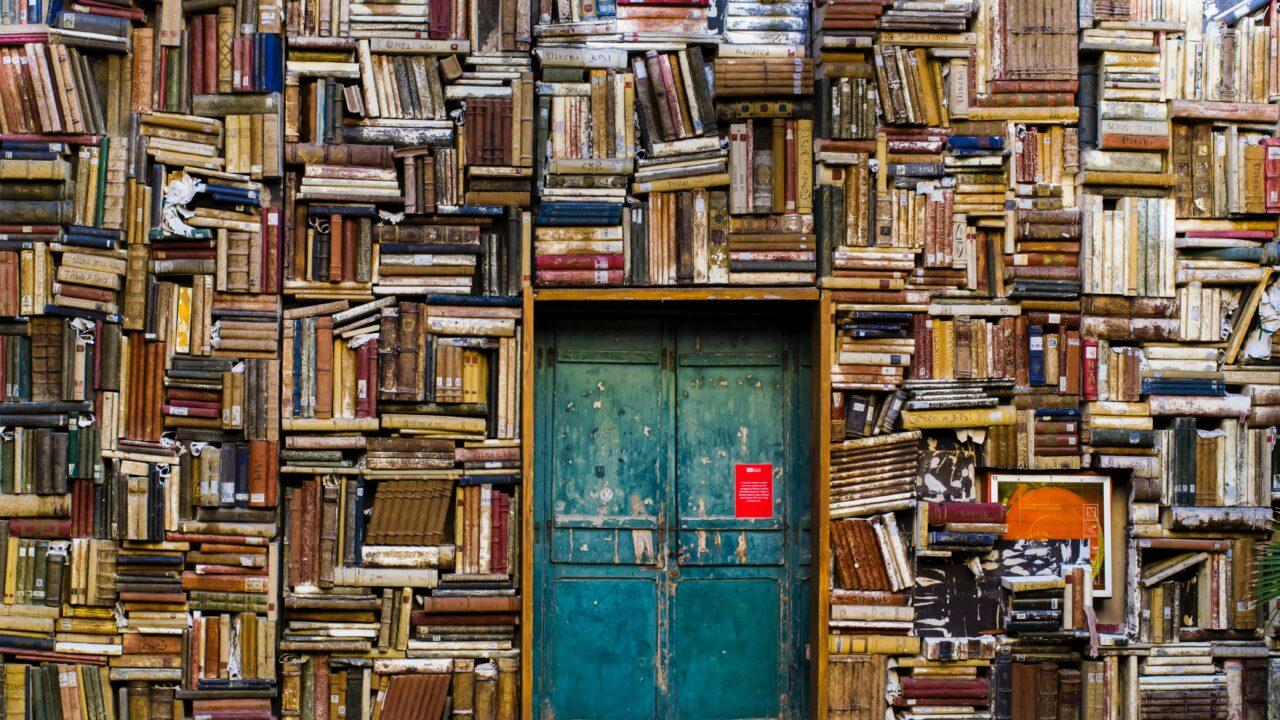 壁にはたくさんの本が積まれており青いドアが中央にある