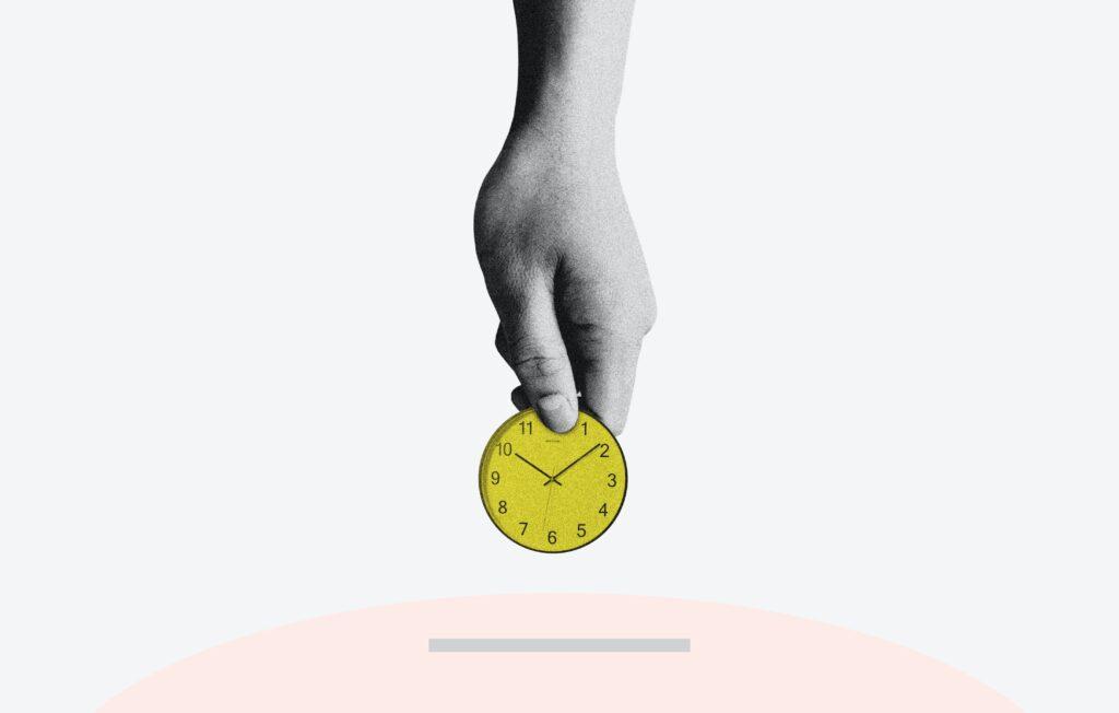 黄色い時計をピンクの箱に入れようとしている手が上から伸びている