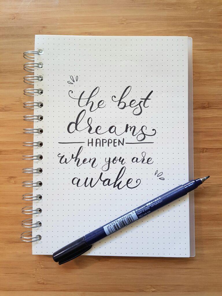 ノートが開かれており、そこに「The best dreams happen when you are awake」と書かれている