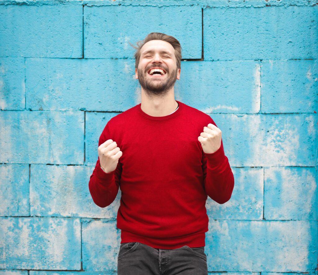 ターコイズの壁の前で赤い服の白人男性がガッツポーズで立っている