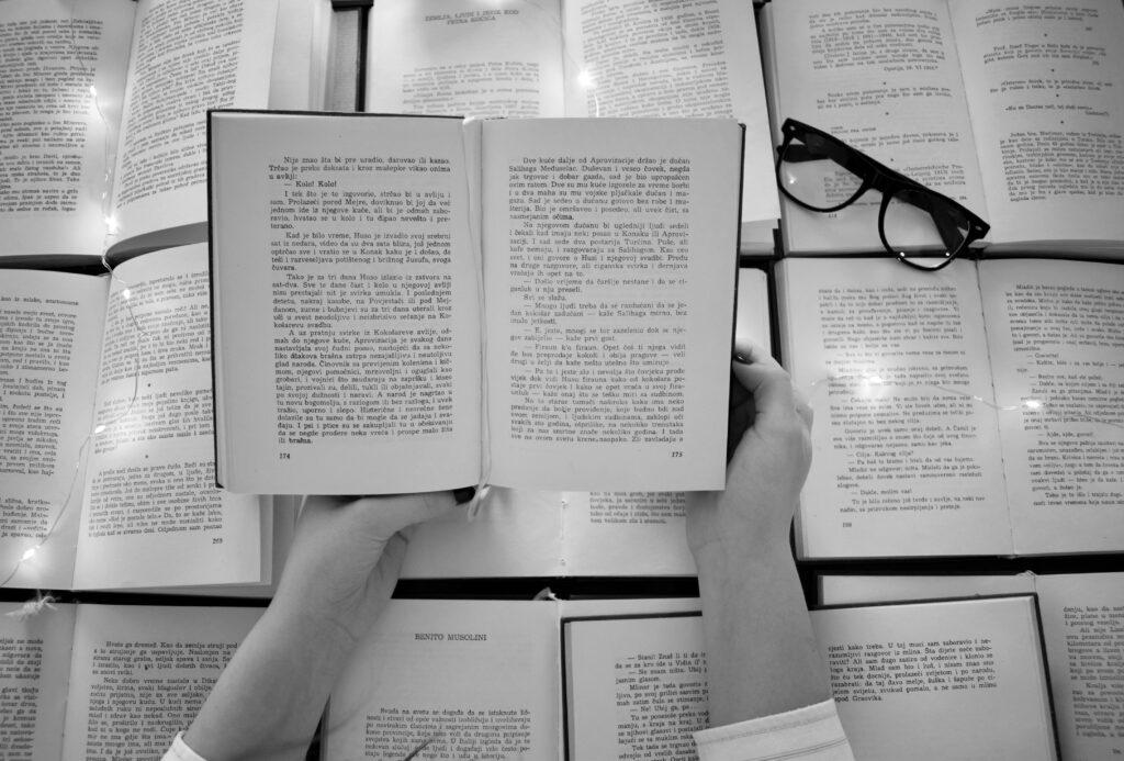本の上にメガネが置いてあり。たくさんの本の中から一冊の本を開いている。