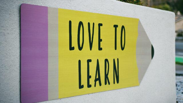 白い壁の鉛筆の形の看板サインにlove to learnと書かれている