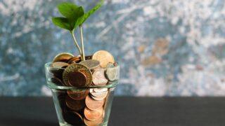 グラスのポットにコインが入っていて植物が生えている