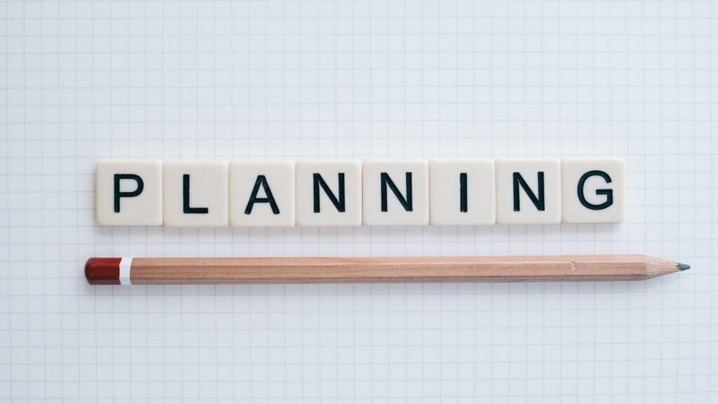 plannningというスクラブルの文字と鉛筆が白い場所に置かれている