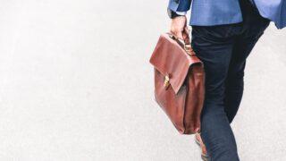 ビジネスマンが茶色いビジネスバッグを持って歩いている