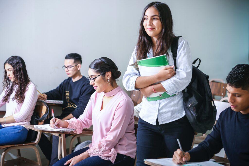 髪の長い若い女性がテキストを抱えて教室に立っている