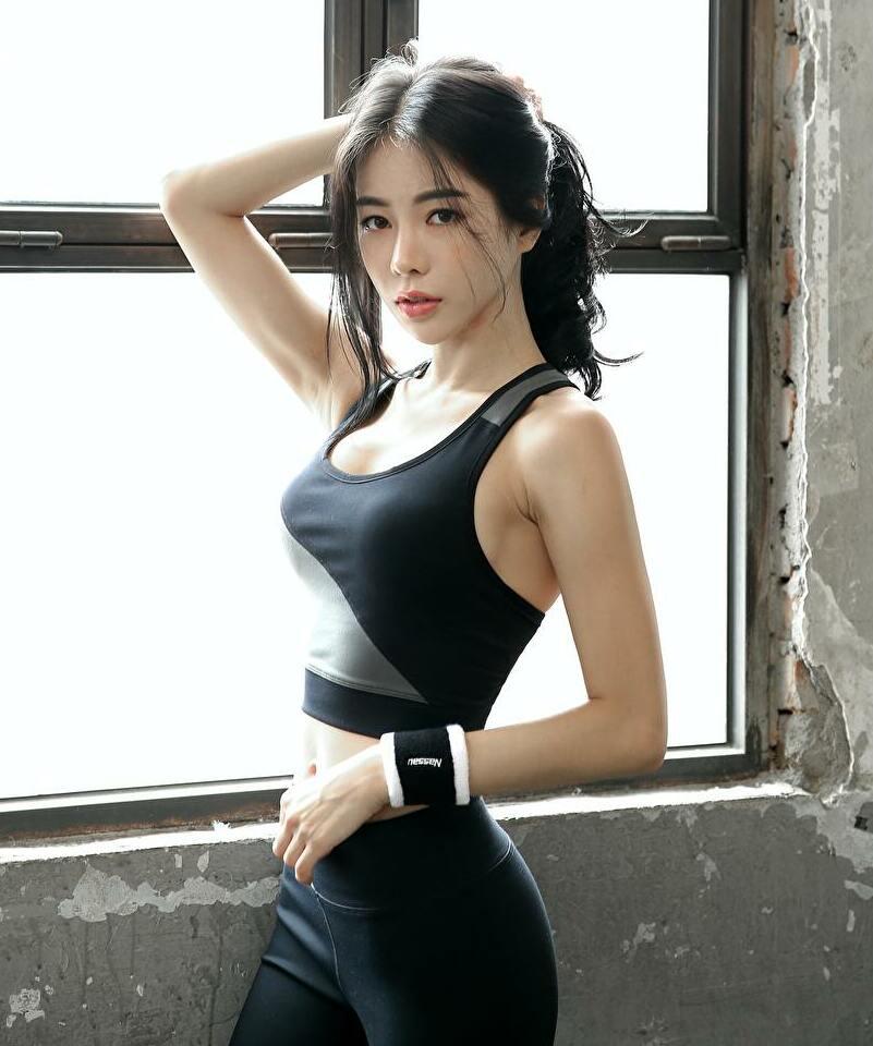 スタイルの良い若い女性が髪を後ろに掴んで窓の前に立っている