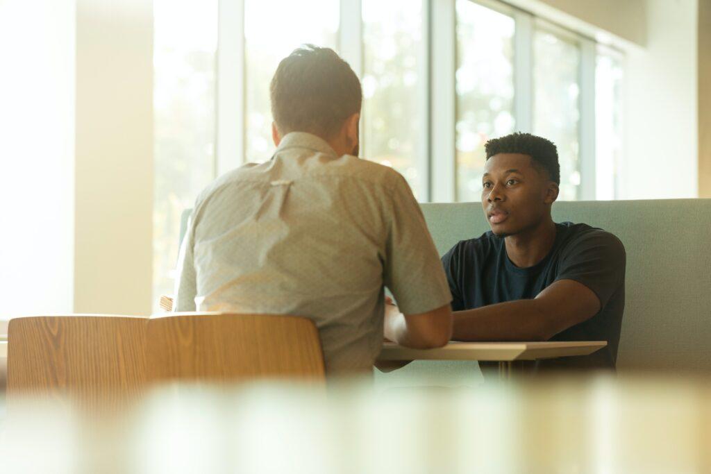 白人男性と黒人男性がテーブルで向かい合って相談している