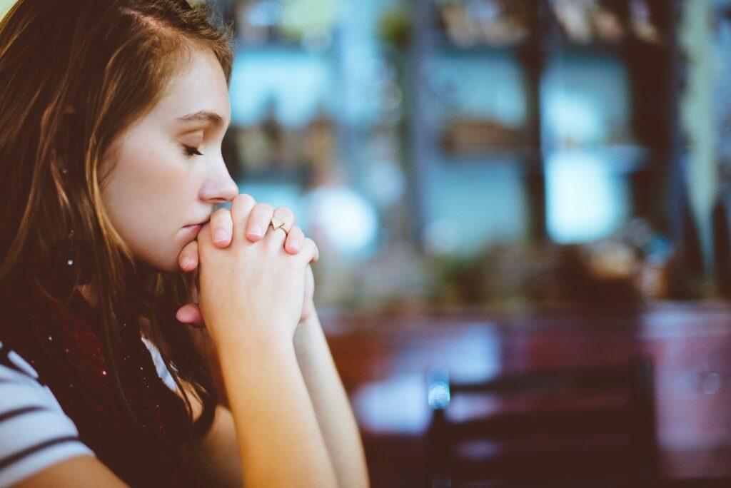 女性が指を絡めてテーブルに座って深く考えている横顔