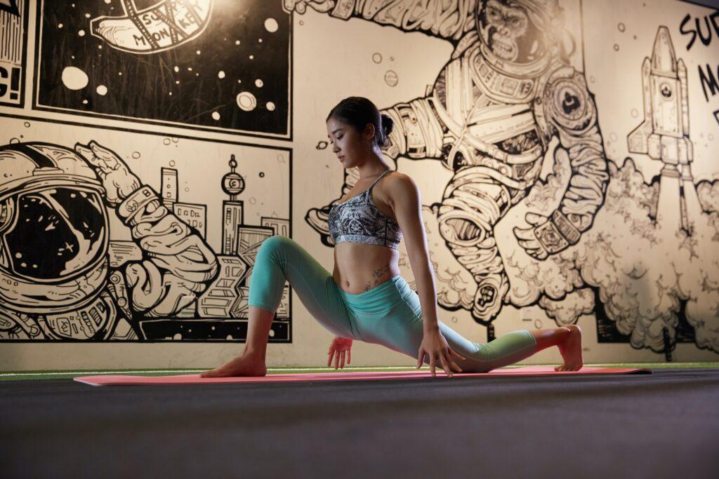 宇宙や宇宙飛行士のイラストが描かれた壁の前で紙をまとめたアジア人の女性がヨガのポーズをとっている