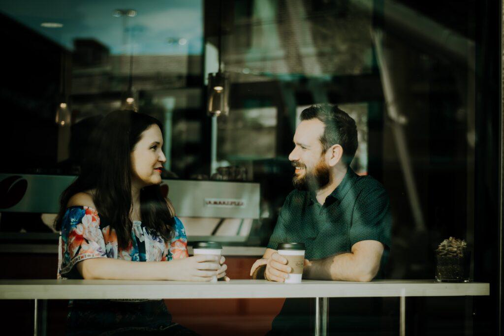 カフェで女性と男性がのテーブルで飲み物を片手に話している