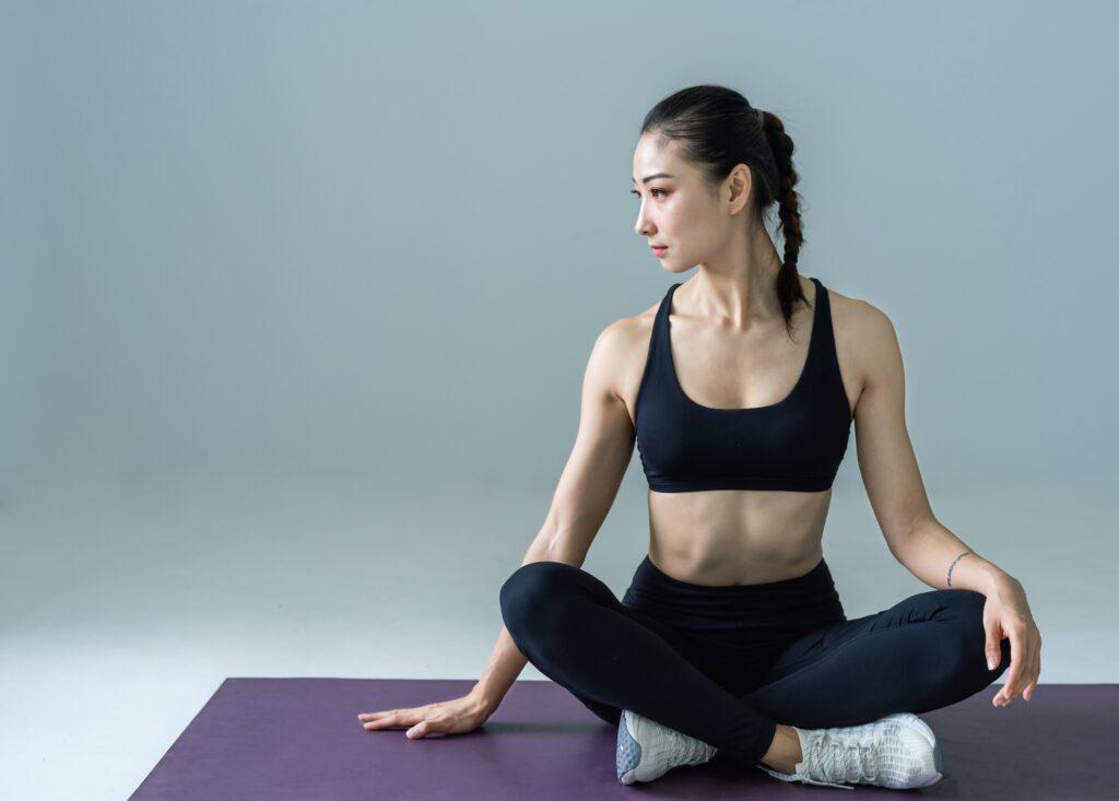 アジアの若い女性がヨガマットの上に右手をついて座っている