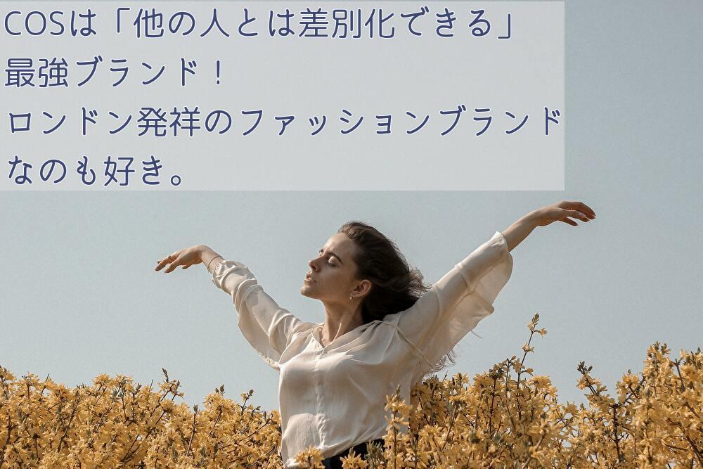 空を背景に黄色の花畑で両手を広げた白いトップと黒いズボンを履いた女性