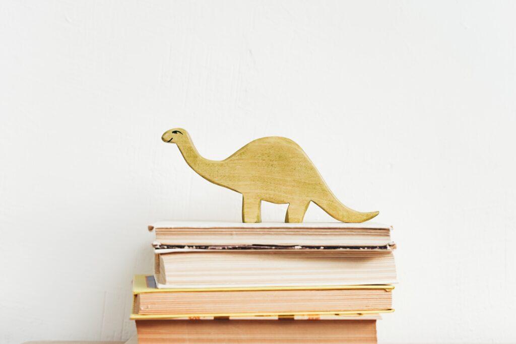 うすい黄色の恐竜の置き物が数冊の本の上に乗っている