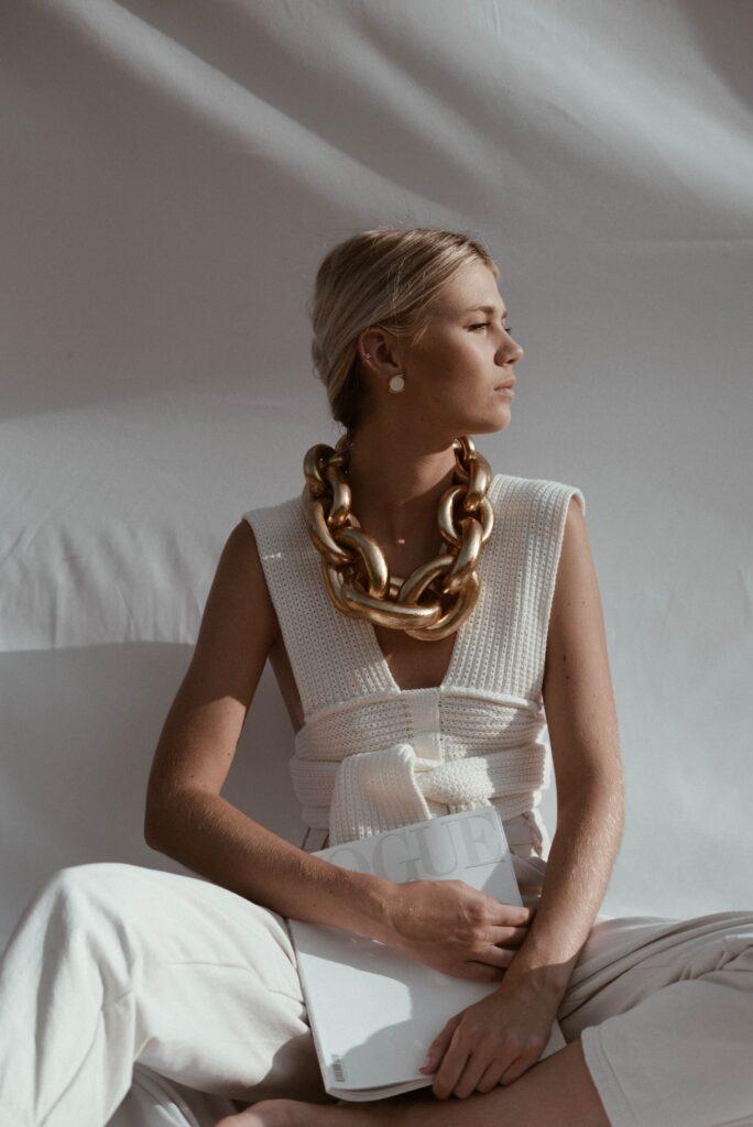 ゴールドの大きいネックレスをして白いノースリーブのベストを着て座っているブロンドの髪をまとめた女性