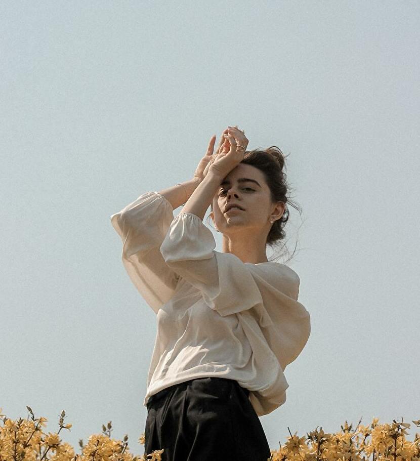 黄色の花畑で、空を背景に髪を束ねた美しい女性が両手を顔の前に置いて白いトップ、黒いズボンを着て立っている