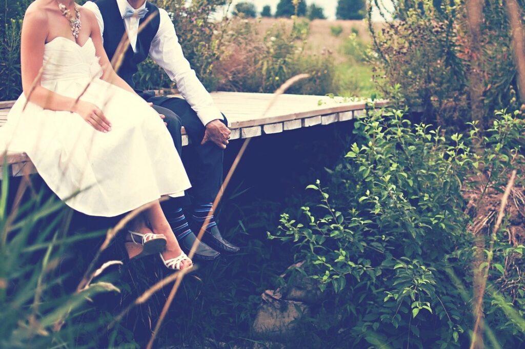 新郎と新婦が野原の橋の上に並んで腰掛けている