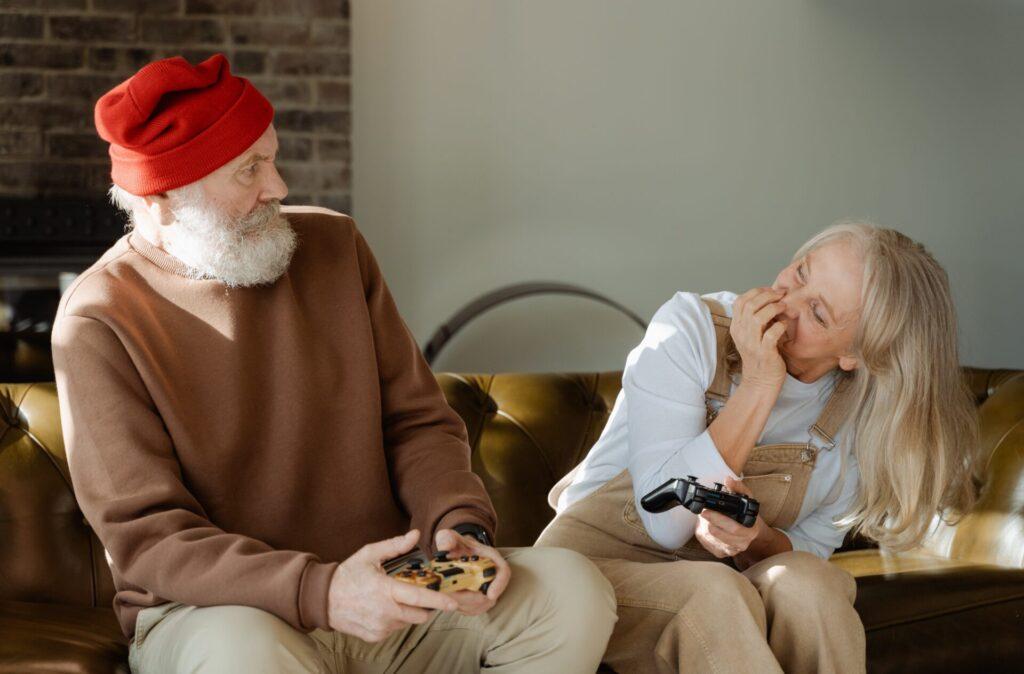 ソファーに座って、テレビゲームをしている高齢者カップル