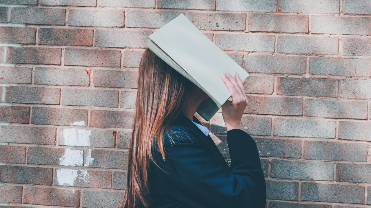 本で顔が覆われている女子学生